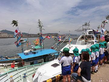 園児に見送られ出港する漁船