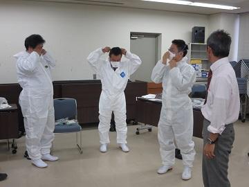 特定家畜伝染病防疫講習会 県職員による防護服着脱の指導