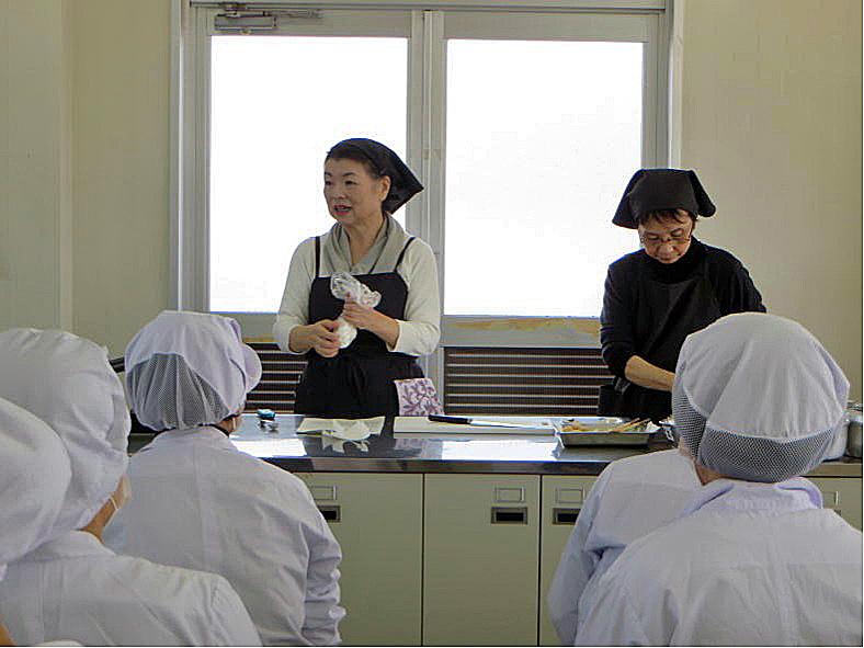 米粉料理の説明をかねてデモを行う様子 (講師:近畿米粉食品普及推進協議会会長 坂本廣子氏・写真左)
